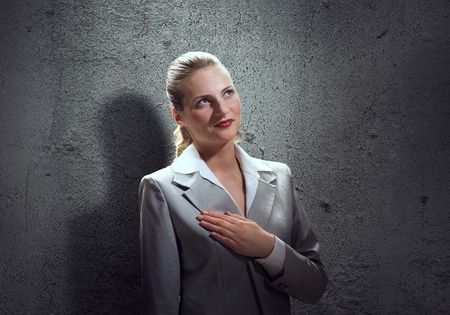 oath: Young businesswoman with hand on chest making an oath Stock Photo