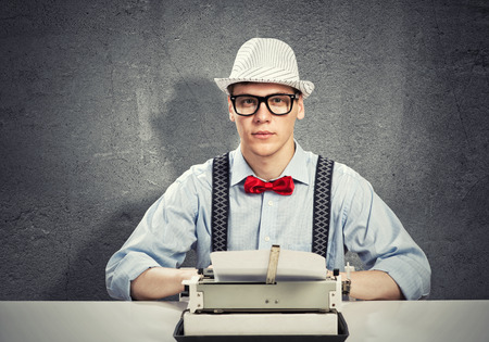 novelist: Young man writer with typing machine waiting for inspiration