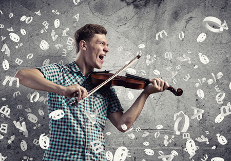 fiddlestick: Young handsome guy playing violin very emotionally Stock Photo