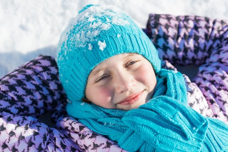 cold weather: Top view of cute girl lying on snow