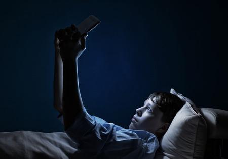태블릿 PC를 사용하는 침대에서 어린 십대 사람