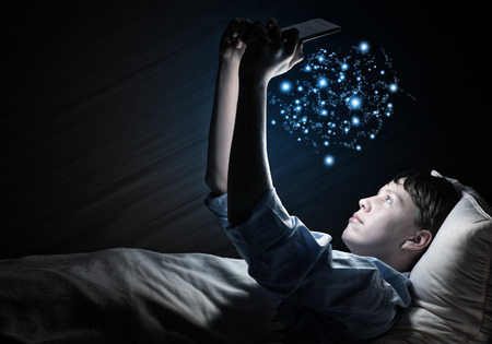 sleeping tablets: Young teenager guy in bed using tablet pc