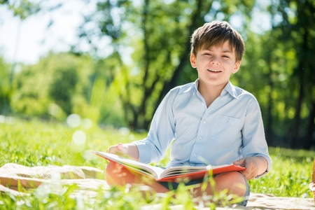 Little adorable boy in sitting park with book in hands photo