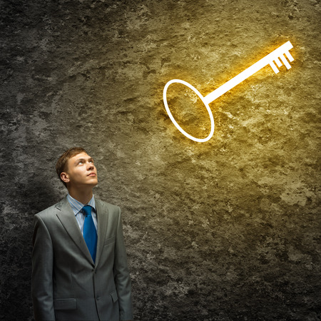 wayout: Young thoughtful businessman looking at key above head Stock Photo