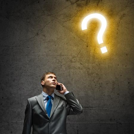 signo de interrogaci�n: Hombre de negocios joven que mira cuidadosamente en signo de interrogaci�n