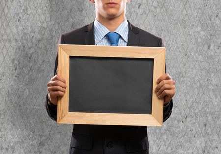 Young businessman holding blank chalkboard. Place for text photo