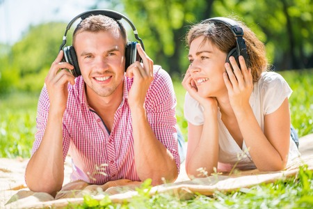 Young couple in summer park listening music photo