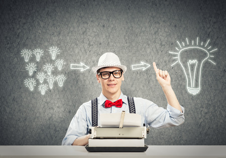 Young guy writer in hat and glasses using typing machine photo