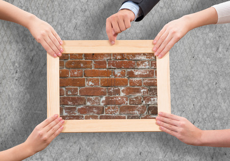 Close up of human hands holding wooden frame with brick texture photo