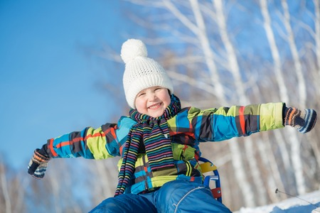 Little cute boy riding sled in winter park photo