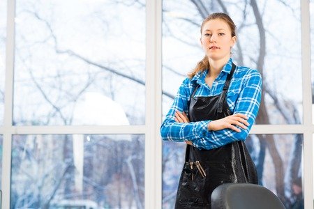 hair stylist: portrait of a woman in a barber shop barber worth apron crossed her arms Stock Photo