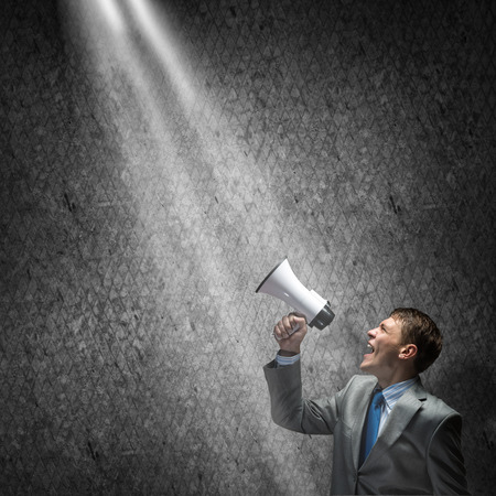 anger management: Young aggressive businessman screaming furiously in megaphone