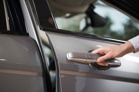 opening up: Close up of human female hand opening car door