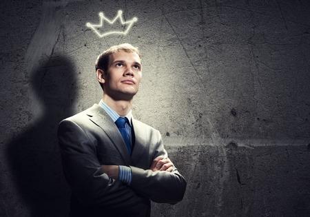 arrogancia: Apuesto hombre de negocios joven con la corona en la cabeza
