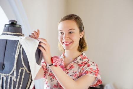 needlewoman: Young pretty needlewoman fitting dress on dummy