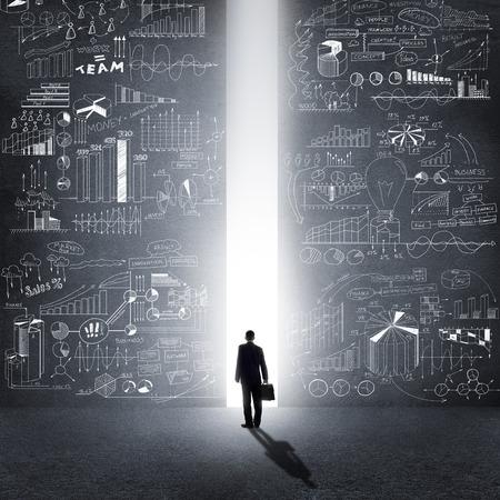 estrategia: Vista trasera del hombre de negocios de pie en la luz de manera