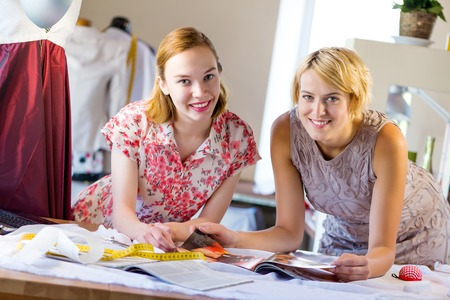 modiste: Two young pretty needlewomen in studio working at order Stock Photo
