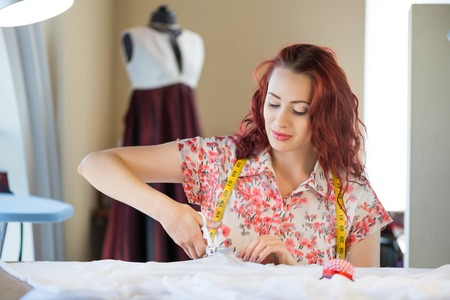 modiste: Young pretty needlewoman cutting fabric with scissors Stock Photo