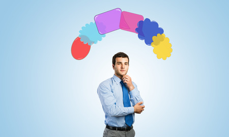 above head: Young thoughtful businessman and colorful speech bubbles above head Stock Photo