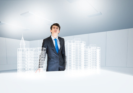 construction project: Young businessman and digital model of construction project