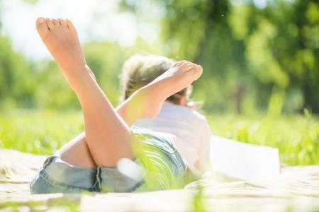 pies bonitos: Vista posterior de la ni�a que miente en parque del verano Foto de archivo