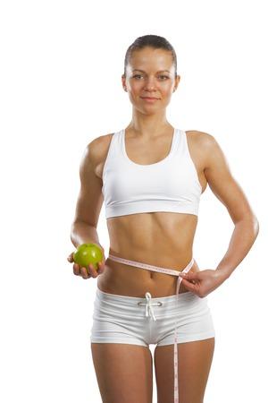 dieta sana: imagen de una mujer joven y atractiva con cinta m�trica y manzana verde
