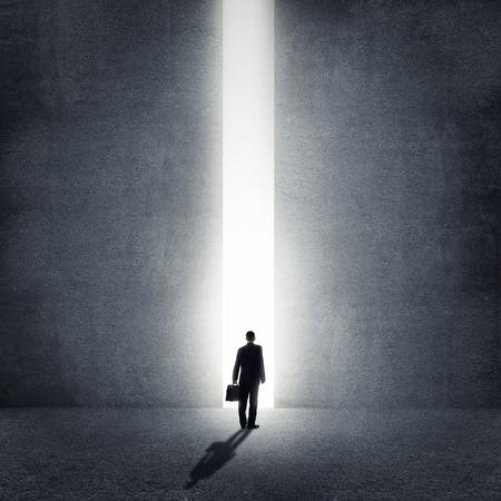 abrir puerta: Vista trasera del hombre de negocios de pie en la luz de manera
