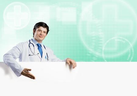 druggist: Young handsome doctor holding white blank banner. Place your text