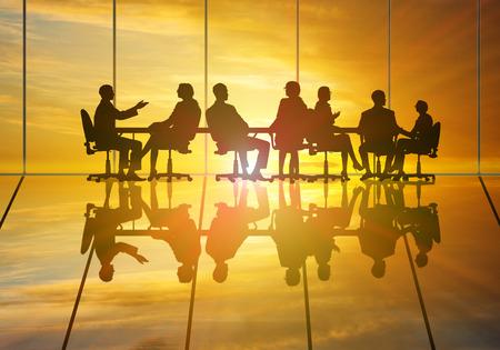 personas saludandose: Siluetas de grupo de hombres de negocios contra la puesta de sol Foto de archivo