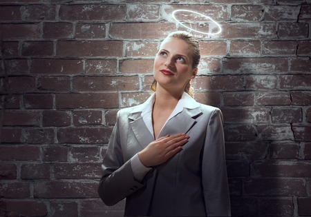 help me: Young saint businesswoman with halo above head Stock Photo
