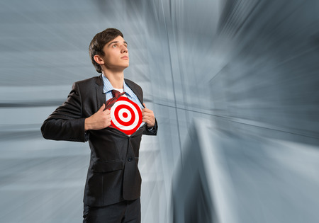 businessman tearing his shirt, under which is a target photo