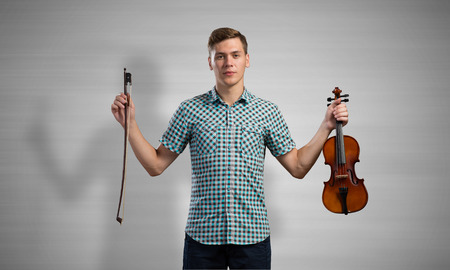 virtuoso: Young handsome guy in shirt playing violin