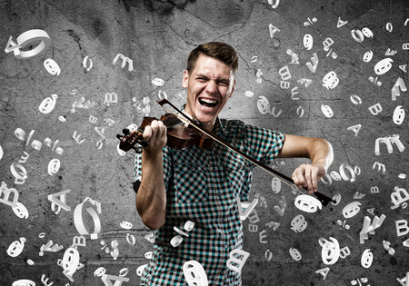 Young handsome guy playing violin very emotionally Stock Photo