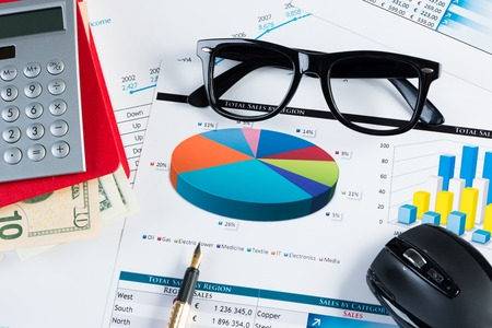 economist: Close of business workplace with financial reports and office stuff Stock Photo