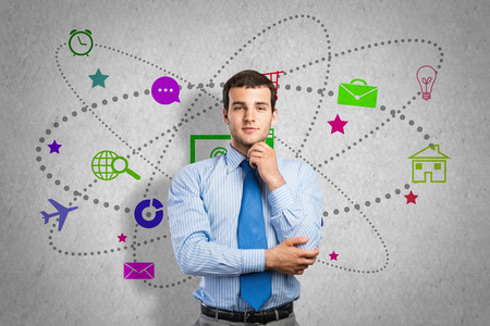 Thoughtful businessman and color application icons at background photo