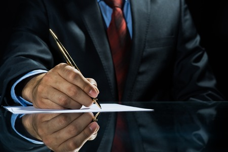 lawyer: Close up of businessman sitting at table and signing document Stock Photo