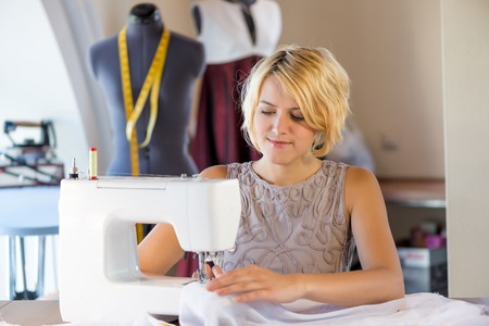 needlewoman: Young attractive needlewoman at studio working with sewing machine