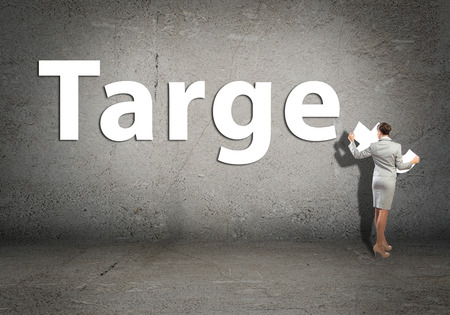 adds: young businesswoman adds target word on concrete wall Stock Photo