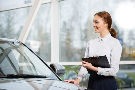 car dealer: Young woman consultant in show room standing near car