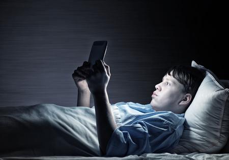 Jonge tiener man in bed met behulp van tablet pc