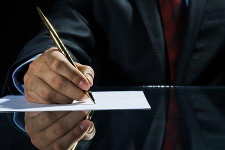Cierre de negocios sentado en la mesa y la firma de documento Foto de archivo - 35629493