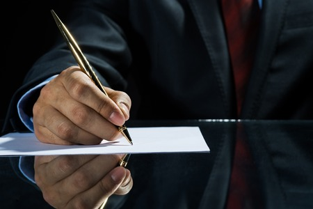 Close up of businessman sitting at table and signing document Banco de Imagens