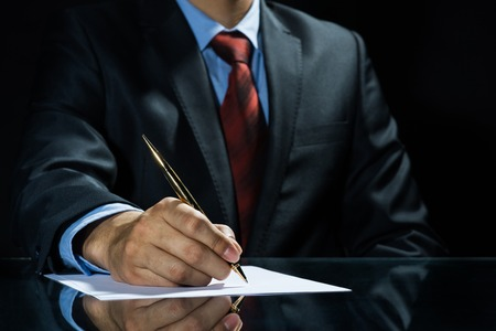 Close up of businessman sitting at table and signing document Stock Photo