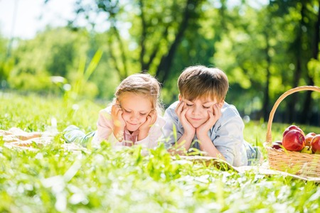 Little adorable children in park laying on grass photo