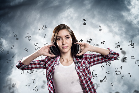Young teenager girl in shirt wearing headphones photo