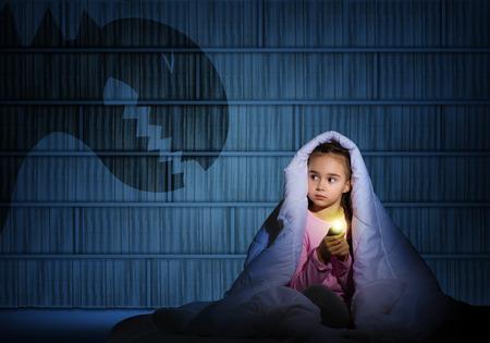 imagen de una niña bajo las sábanas con una linterna la noche miedo a los fantasmas Foto de archivo