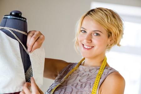 needlewoman: Young blonde needlewoman fitting dress on dummy