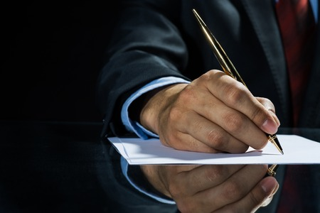 businessman signing documents: Close up of businessman sitting at table and signing document Stock Photo