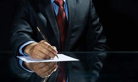 Close up of Geschäftsmann sitzt am Tisch und Unterzeichnung Dokument Lizenzfreie Bilder