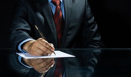 Close-up van zakenman zitten aan tafel en het ondertekenen van het document